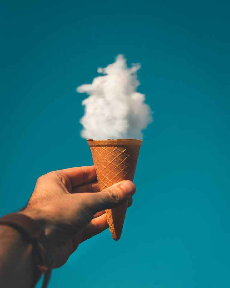 man holding ice cream cone under cloud